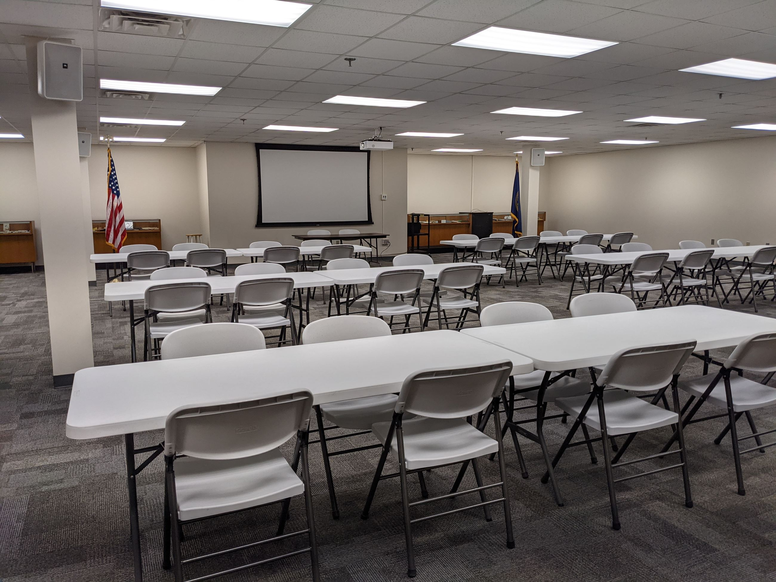 Photo showing the Large Meeting Room with tables, chairs, and projection system.